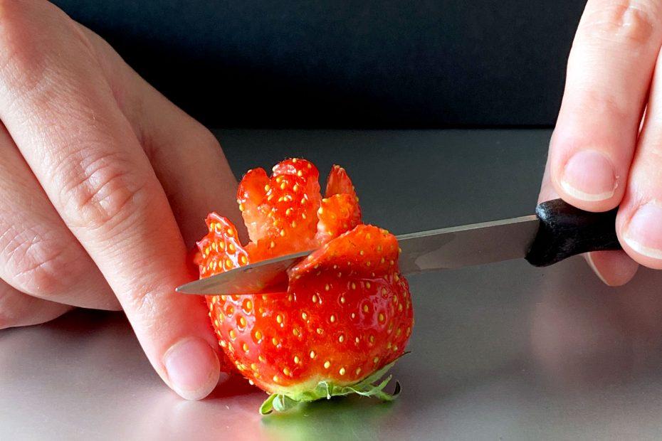 Rose aus Erdbeere mit einem Messer schneiden