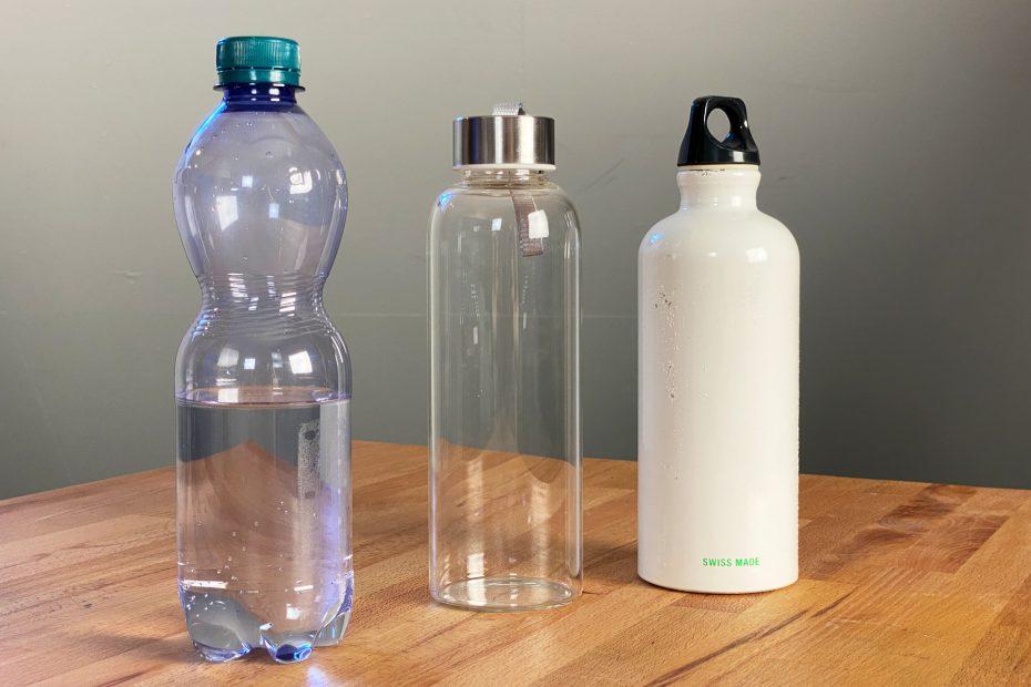 Plastikflasche neben Flasche aus Glas und Alu